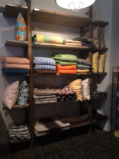 Ladder, shelving unit with display of colourful blankets and cushions