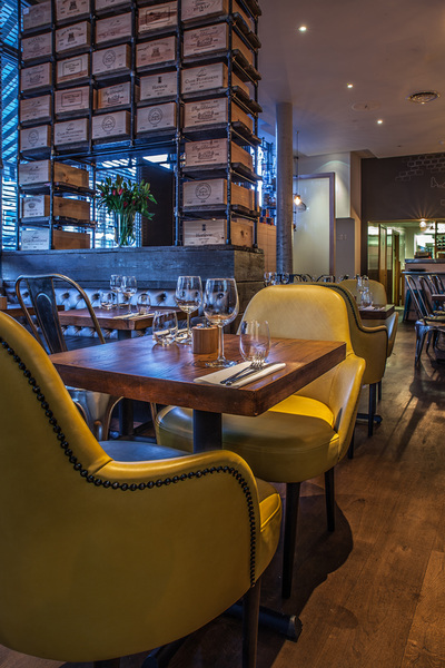 Contemporary restaurant interior with yellow, studded, upholstered chairs and bespoke industrial shelving with reclaimed wine box drawers