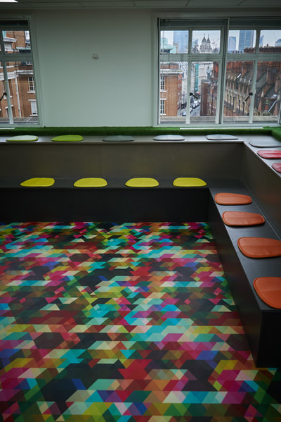 Tiered seating made from grey Valchromat with multi coloured seat pads and Pop Geometric vinyl flooring by Atrafloor