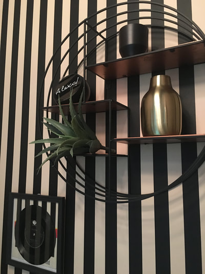 Circular shelf unit from Graham and Green with Alexa Spot on black and white stripy wallpaper