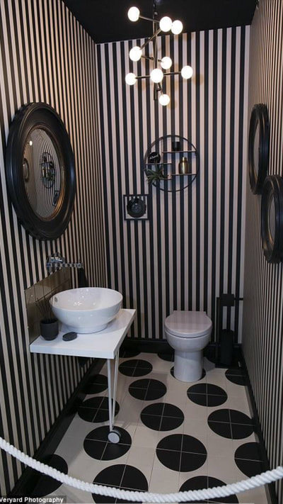 Lavatory with bowl sink on a freestanding vanity shelf, gold glass, splashback tiles, black and gold convex wall mirrors, spotty floor tiles and stripy wallpaper and black toilet roll holder with black toilet paper