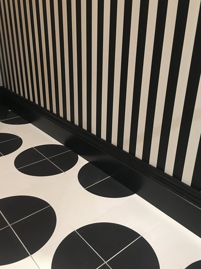 Lavatory with, black and white polka dot floor tiles from Designworks, Clerkenwell, black and white, vertical striped wallpaper and black skirting board
